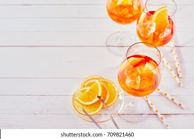 Refreshing aperol spritz cocktails with straws and sliced orange on a white timber table.