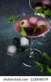 Refreshing blackberry juice on dark background. Cold summer berry drink Mojito with ice and mint