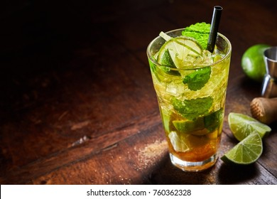 Refreshing chilled mint julep cocktail served on crushed ice with lime in a high angle view on a wooden bar counter with copy space