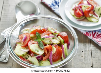 A refreshing classic summer salad often found at cookouts and picnics is made with tomatoes, cucumber, onion and mint.  Selective focus was used on this image.