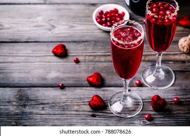 Refreshing cocktail with champagne and cranberry for Valentine's day on wooden background