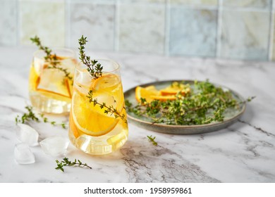 Refreshing cocktail with ice, orange and thyme. Refreshing summer homemade alcoholic or non-alcoholic cocktail or mocktail, or Detox infused flavored water.