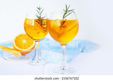 Refreshing cocktail with ice, oranges and rosemary in glasses over white background.