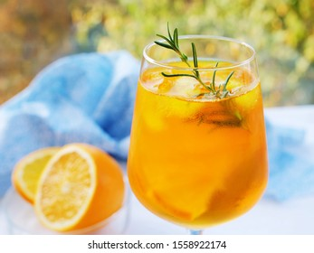 Refreshing cocktail with ice, rosemary and orange slice in glass with condensation over an outdoor table.