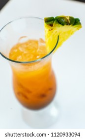 Refreshing Cocktail of liqueurs, natural tea, natural juices and vodka in a glass cup and a piece of pineapple detail.