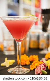 A refreshing cocktail in a martini glass with carnation decorative accents.