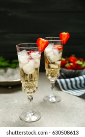 Refreshing cocktails with strawberry on gray table