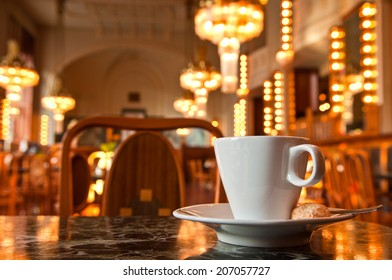 Refreshing coffee with a backdrop of Art Deco lighting in Prague cafe, Czech Republic.