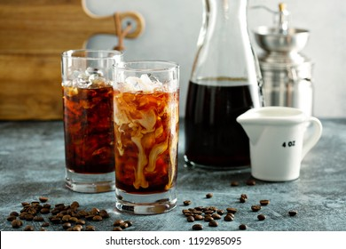 Refreshing cold brew iced coffee in tall glasses with milk or creamer