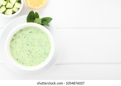 Refreshing cold cucumber, yogurt, mint and lemon soup in bowl, photographed overhead on white wood (Selective Focus, Focus on the soup)