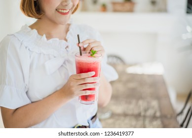 Refreshing cold summer drink watermelon juice. woman holding glass tropical fresh drink at cafe.