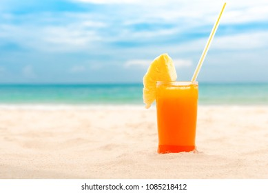 Refreshing cold tropical fruit punch drink garnished with pieapple in summer white sand beach background with copy space
