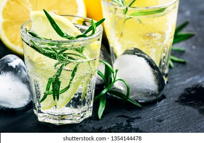 Refreshing cool summer lemon drink with rosemary, ice and gin tonic, black stone bar counter background, copy space, selective focus