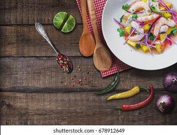 Refreshing dish of fish marinated in citrus juice on wooden table. Shrimp and Mango Ceviche. Diet and healthy food concept