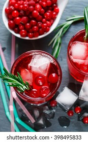 A refreshing drink of cranberry, rosemary and ice cubes. Selective focus. Top view