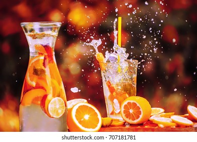 Refreshing drink in a glass cup with frutkov, slices of oranges and lemons vokurg. Splash from the glass in motion. Spraying into the sides chilled drink in a glass. Red colors and background