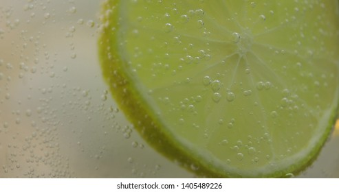 A refreshing drink in a glass with ice, and lime. Mineral water in the glass with ice cubes. Soda tonic fizzy water