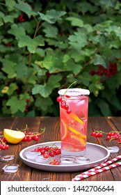 Refreshing drink, homemade lemonade with red currants and ice cubes in a glass on a wooden background