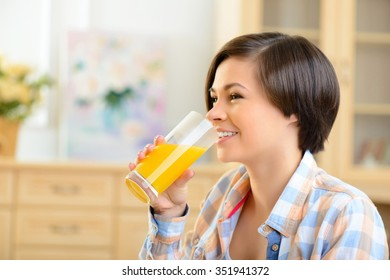 Refreshing drink. Young appealing teenage girl enjoying a glass of orange juice.