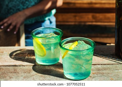 Refreshing drinks with ice and lemon slices on bar table.