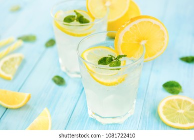 Refreshing drinks for summer, cold sweet and sour lemonade juice with ice cubes in the glasses garnished with sliced fresh lemons