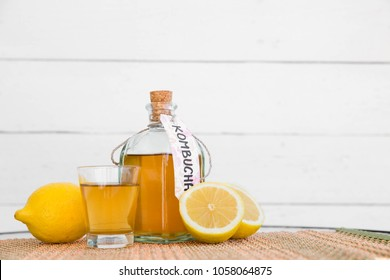 Refreshing filtered kombucha tea in a glass bottle and a glass, with label written kombucha on it, white wooden background.