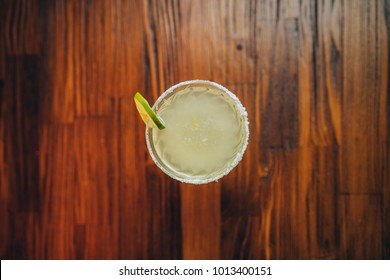 Refreshing fresh classic lime margarita cocktail in margarita glass with lemon on wooden table from top view. Vintage retro bar interior design.