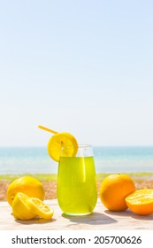 Refreshing fruity juice with the fresh lemon and orange on the wood with sea scenery
