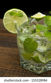 refreshing gin tonic on the wooden table on black background