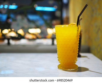 Refreshing with a glass of Iced Yuzu orange mixed with honey and lemon juice on marble table. Selective focus.
