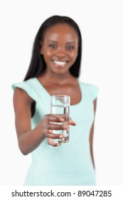 Refreshing glass of water offered by young woman against a white background