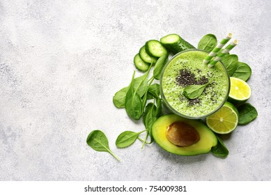 Refreshing green smoothie with spinach, avocado, cucumber and banana in a tall glass over light slate, stone or concrete background.Top view with copy space.