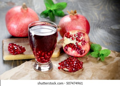Refreshing and healthy pomegranate juice and pomegranate fruit on table
