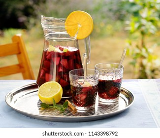 Refreshing homemade sangria with summer fruits in pitcher and glasses