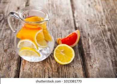 Refreshing ice cold water with lemon and grapefruit on a wooden background. Concept of diet.  Diet for weight loss.