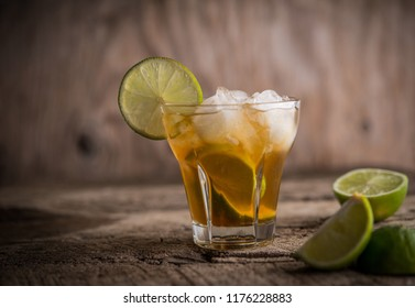 Refreshing ice drink with lime over wooden background