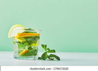 Refreshing ice mint cocktail with ice cubes, orange and lemon slices, drink for hot summer days. Fresh cool lemon-mint water, cocktail, detox drink, lemonade in glass jar and glass - Shutterstock ID 1798172020