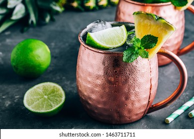 Refreshing Iced Cold Moscow Mule cocktail with lime and pineapple on dark background