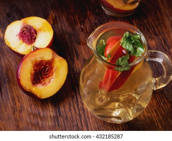 Refreshing iced green tea with peaches and mint, served in a glass with ice cubes and brown sugar on rustic wooden board, selective focus