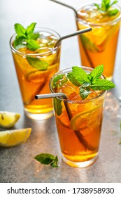 Refreshing iced tea with lemon and mint, cold summer drink with reusable metal straws