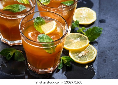 refreshing iced tea with mint and lemon on dark background, closeup, horizontal