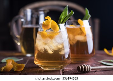 Refreshing iced tea with whiskey, honey, citron and sage on rustic wooden background. Selected focus