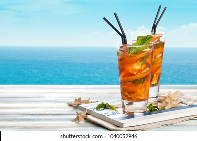 Refreshing lemonade with oranges and mint on wooden table.
