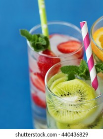A refreshing lemonade with strawberry, orange, mint and ice. Useful summer drinks on a blue background.