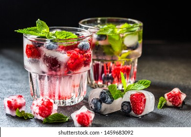 Refreshing lemonade without sugar, with raspberries, blueberries and ice cubes on a dark background. Summer conceptual drink.