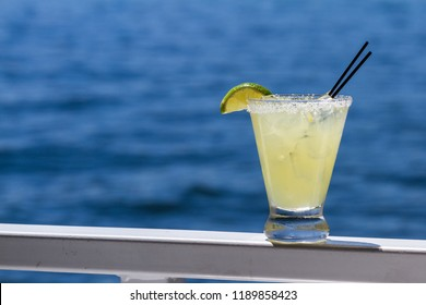 refreshing margarita served outside with a water background as a travel concept
