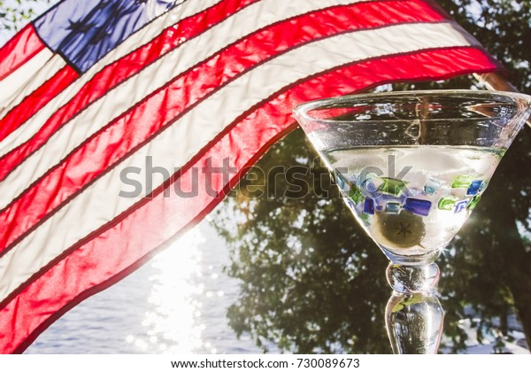 A refreshing martini with the cool waters of a lake in the background