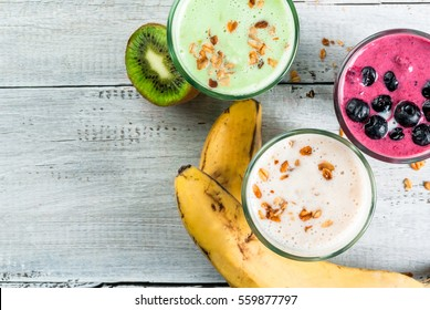 Refreshing milkshakes or smoothies: White (banana), green (apple and kiwi) and berries. On a white wooden table, copy space, top view