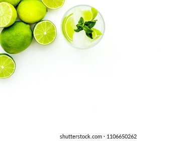 Refreshing mojito cocktail. Slices of lime, mint, glass with ice cubes on white background top view space for text