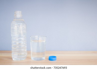 Refreshing natural mineral water in plastic bottle with transparent glass on wooden desk with copyspace